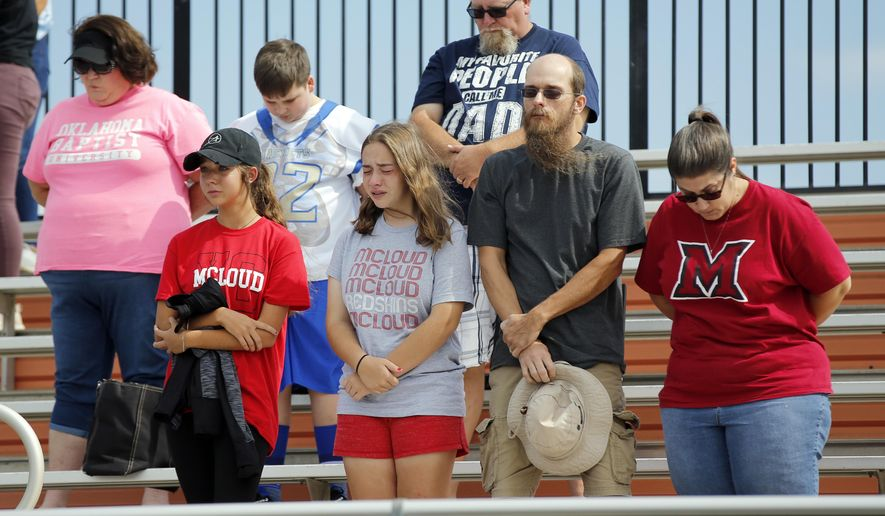 In this Saturday, Oct. 6, 2018, photo, McLoud High School fans stand for a moment of silence honoring Kaylen Thomas before a high school football game between McLoud and Cushing at O'Dell Field in Cushing, Okla. The game was postponed and moved from McLoud after Thomas, a McLoud High School student, was fatally shot the previous day. (Nate Billings/The Oklahoman via AP)