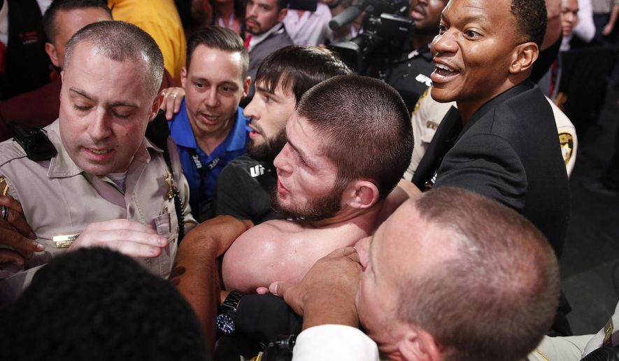 Khabib Nurmagomedov, bottom center, is held back outside of the cage after fighting Conor McGregor in a lightweight title mixed martial arts bout at UFC 229 in Las Vegas, Saturday, Oct. 6, 2018. Nurmagomedov won the fight by submission during the fourth round to retain the title. (AP Photo/John Locher) **FILE**