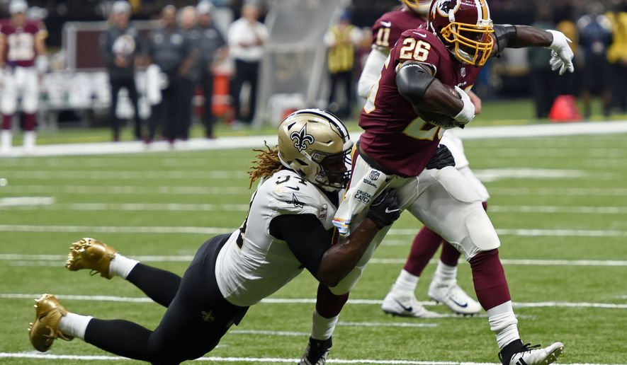 Washington Redskins running back Adrian Peterson (26) caries against New Orleans Saints defensive end Cameron Jordan (94) in the first half of an NFL football game in New Orleans, Monday, Oct. 8, 2018. (AP Photo/Bill Feig)