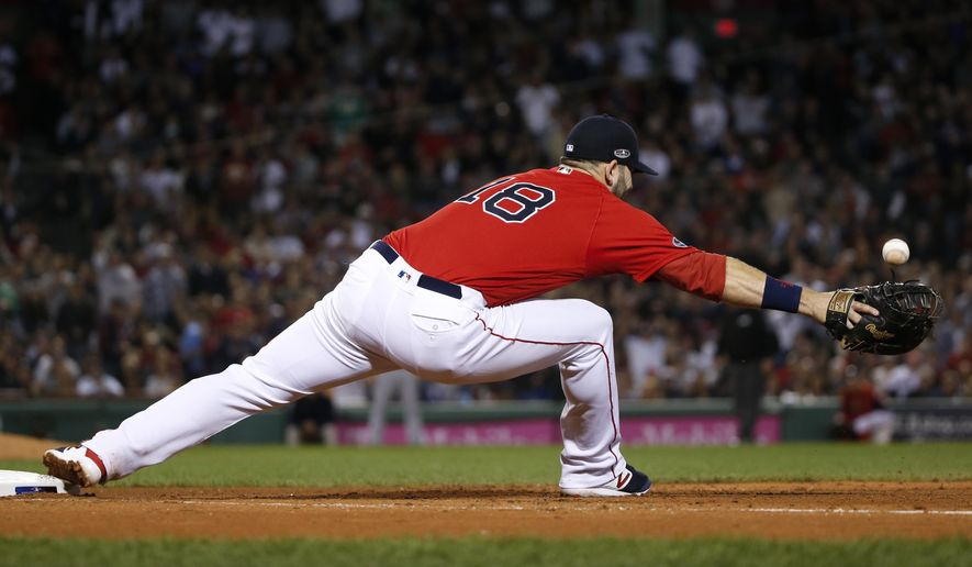 Boston Red Sox first baseman Mitch Moreland cannot get a glove on a throw to first after a base hit by New York Yankees' Aaron Judge during the fifth inning of Game 2 of a baseball American League Division Series, Saturday, Oct. 6, 2018, in Boston. (AP Photo/Elise Amendola)
