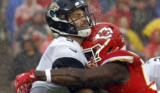 Jacksonville Jaguars quarterback Blake Bortles, left, is hit by Kansas City Chiefs linebacker Justin Houston, right, after throwing a pass during the first half of an NFL football game in Kansas City, Mo., Sunday, Oct. 7, 2018. (AP Photo/Charlie Riedel)