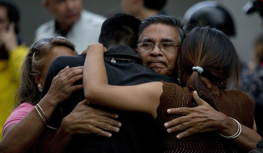 Staff members of jailed councilman Alberto Alban Salazar embrace outside the Bolivarian National Security Service (SEBIN) headquarters in Caracas, Venezuela, Monday, Oct. 8, 2018. Venezuela's Attorney General Tarek William Saab said Monday that Salazar, who was arrested on suspicion of involvement in a failed assassination attempt on President Nicolas Maduro, has died of suicide. (AP Photo/Fernando Llano)