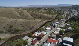 FILE - This April 2, 2017 file photo made with a drone, shows the U.S. Mexico border fence as it cuts through the two downtowns of Nogales, Ariz. The Arizona Attorney General's Office is seeking more funding to ease the burden brought by a rise in cases at the border. (AP Photo/Brian Skoloff, File)