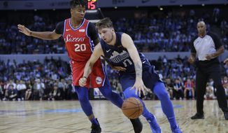 Luka Doncic of the Dallas Mavericks, right, controls the ball past Markelle Fultz of the Philadelphia 76ers, during the Shenzhen basketball match between the Philadelphia 76ers and the Dallas Maverick, part of the NBA China Games, in Shenzhen city, south China's Guangdong province, Monday, Oct. 8, 2018. (AP Photo/Kin Cheung)