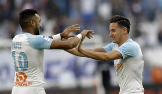 Marseille's Florian Thauvin, right, celebrates with teammate Dimitri Payet after scoring his side's second goal during the League One soccer match between Marseille and Caen at the Velodrome stadium, in Marseille, southern France, Sunday, Oct. 7, 2018. (AP Photo/Claude Paris)