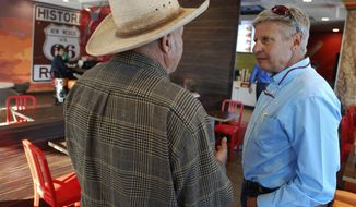 Libertarian U.S. Senate candidate Gary Johnson, right, talks with disabled military veteran Henry Pacheco during a campaign stop in Tucumcari, N.M. Former governor of New Mexico and two-time presidential candidate Gary Johnson says he would act as an influential swing vote and a voice of reason in a bitterly divided Senate.AP Photo/Morgan Lee)