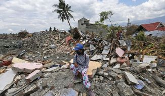 A woman sits on a pile of rubble in an area devastated by an earthquake in the Balaroa neighborhood of Palu, Central Sulawesi, Indonesia, Monday, Oct. 8, 2018. Aid has begun pouring into central Indonesia's Sulawesi island and humanitarian workers are fanning out across its countryside, more than a week after parts of the island were devastated by a powerful earthquake and tsunami. (AP Photo/Dita Alangkara)