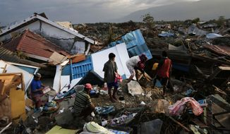 In this Friday, Oct. 5, 2018, photo, a family scavenges for salvageable items from the ruins of their house at Petobo neighborhood which was wiped out by liquefaction caused by a massive earthquake in Palu, Central Sulawesi, Indonesia. Many in the decimated village had no idea they were in an area already identified as a high-risk zone for this apocalyptic phenomenon that causes soft ground to liquefy during temblors. The area around Sulawesi island's Palu Bay had been slammed before and was due for another potential perfect storm, capable of unleashing earthquakes, landslides, tsunami waves, and soil liquefaction. (AP Photo/Dita Alangkara)