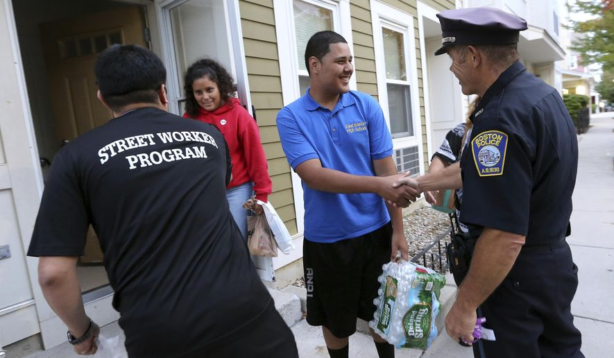 In this Sept. 20, 2018, photo, Francisco Melger, left, of the Boston Center for Youths and Family, and Police Officer Dan Long greet East Boston residents during a Walk for Peace and Unity. Nearly three years after the nation's largest single takedown of MS-13 gang members, residents in the strongly Central American communities around Boston say the streets are noticeably quieter. (AP Photo/Elise Amendola)