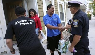 In this Sept. 20, 2018, photo, Francisco Melger, left, of the Boston Center for Youths and Family, and Police Officer Dan Long greet East Boston residents during a Walk for Peace and Unity. Nearly three years after the nation's largest single takedown of MS-13 gang members, residents in the strongly Central American communities around Boston say the streets are noticeably quieter. (AP Photo/Elise Amendola) **FILE**