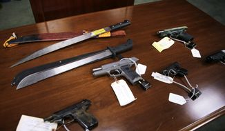 This Jan. 29, 2016, file photo shows weapons on display at the U.S. Attorney's office following the arrests of gang members in Boston. Nearly three years after the nation's largest single takedown of MS-13 gang members, residents of strongly Central American communities in the Boston area say the streets are noticeably quieter. (AP Photo/Charles Krupa, File)