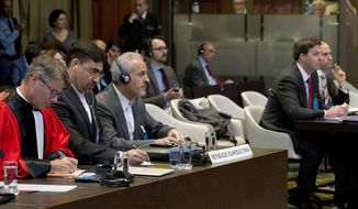 In this Wednesday Oct. 3, 2018, image Mohammed Zahedin Labbaf, third left, agent for the Islamic Republic of Iran, and the U.S. delegation, right, listen to the ruling of the judges on an Iranian request to order Washington to suspend sanctions against Tehran, at the International Court of Justice, or World Court, in The Hague, Netherlands. The U.S. is urging the United Nations' highest court Monday Oct. 8, 2018, to toss out a case filed by Iran that seeks to recover around $2 billion worth of frozen assets the U.S. Supreme Court awarded to victims of a 1983 bombing in Lebanon and other attacks linked to Iran.(AP Photo/Peter Dejong)