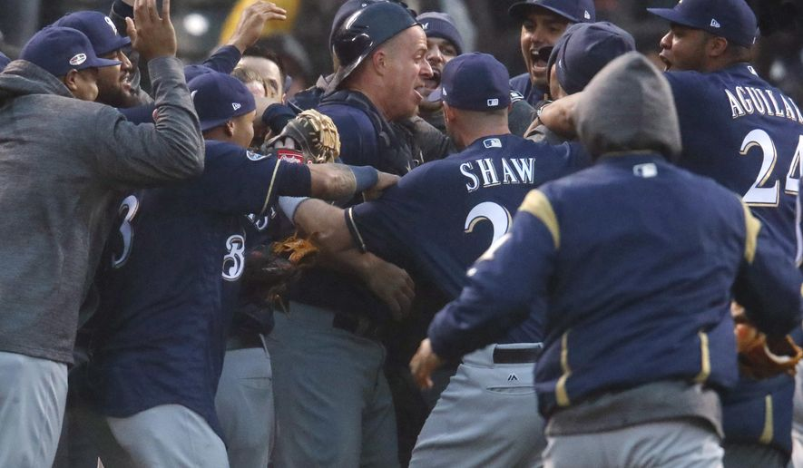 Milwaukee Brewers catcher Erik Kratz, center, is swarms by teammates after the Colorado Rockies committed the final out in the ninth inning of Game 3 of a baseball National League Division Series Sunday, Oct. 7, 2018, in Denver. The Brewers won 6-0 to sweep the series in three games and move on to the National League Championship Series. (AP Photo/David Zalubowski)