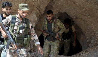 FILE - In this Sunday, Sept. 9, 2018 file photo, fighters with the Free Syrian army exit a cave where they live, in the outskirts of the northern town of Jisr al-Shughur, Syria, west of the city of Idlib. Turkey's state-run Anadolu Agency news agency said Monday, Oct. 8, 2018, that Syrian rebels have finished withdrawing all their heavy weapons from the front lines in the northwestern province of Idlib. The move was part of a deal reached between Russia and Turkey to demilitarize the front lines between Syrian government forces and the opposition in and around the province. Idlib is the last major rebel stronghold in Syria. (Ugur Can/DHA via AP, File)
