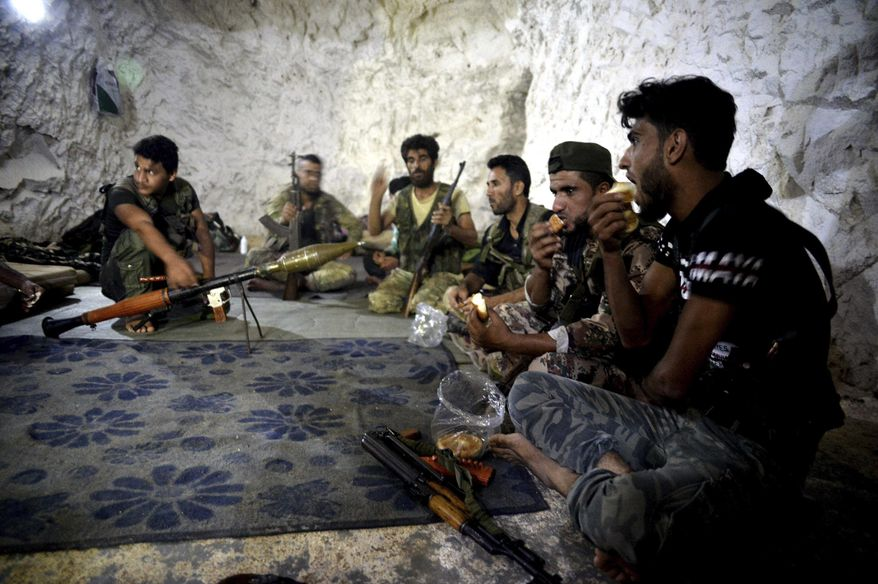 FILE - In this Sunday, Sept. 9, 2018 file photo, fighters with the Free Syrian army eat in a cave where they live, on the outskirts of the northern town of Jisr al-Shughur, Syria, west of the city of Idlib. Turkey's state-run Anadolu Agency news agency said Monday, Oct. 8, 2018, that Syrian rebels have finished withdrawing all their heavy weapons from the front lines in the northwestern province of Idlib. The move was part of a deal reached between Russia and Turkey to demilitarize the front lines between Syrian government forces and the opposition in and around the province. Idlib is the last major rebel stronghold in Syria. (Ugur Can/DHA via AP, File)