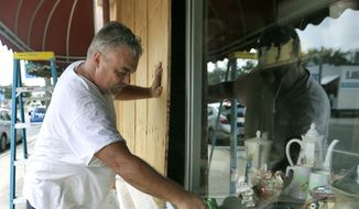 Bobby Smith boards up the windows at Jani's Ceramics in Panama City, Fla., on Monday, Oct. 8, 2018, in preparation for the arrival of Hurricane Michael. (Patti Blake/News Herald via AP)