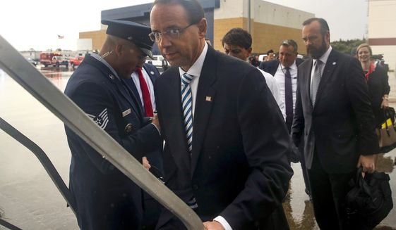 Deputy Attorney General Rod Rosenstein boards Air Force One in the rain, Monday, Oct. 8, 2018, in Orlando, Fla. (AP Photo/Alex Brandon)