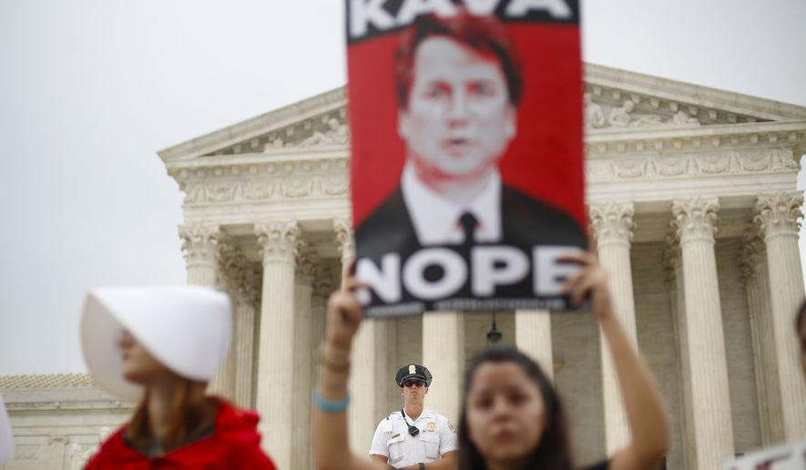A police officer guards the front steps of the Supreme Court in Washington as activists protest, Tuesday, Oct. 9, 2018. A Supreme Court with a new conservative majority takes the bench as Brett Kavanaugh, narrowly confirmed after a bitter Senate battle, joins his new colleagues to hear his first arguments as a justice. (AP Photo/Pablo Martinez Monsivais)