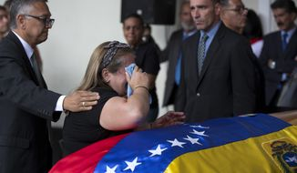 Luz Alban, the sister of opposition activist Fernando Alban, is consoled as she cries next to the flag-draped casket containing his remains, during a solemn ceremony at the National Assembly headquarters, in Caracas, Venezuela, Tuesday, Oct. 9, 2018. International condemnation of Venezuelas leadership poured in Tuesday following the suspicious death of the opposition activist authorities say evaded justice by throwing himself from the 10th floor of a police building. (AP Photo/Ariana Cubillos)