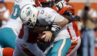 FILE - In this Oct. 7, 2018, file photo, Cincinnati Bengals defensive tackle Geno Atkins sacks Miami Dolphins quarterback Ryan Tannehill (17) during the second half of an NFL football game, in Cincinnati.  Atkins sacked Ryan Tannehill twice and hit him three other times as he was getting rid of the ball. The Bengals defensive tackle simply pushed through the Miami Dolphins' line, his latest disruptive performance in an impressive start to the season. (AP Photo/Frank Victores, File)