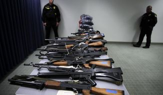Two deputies stand near illegally possessed firearms seized by authorities, shown at a news conference in Los Angeles Tuesday, Oct. 9, 2018. Officials say a new police task force targeting people who aren't allowed to have guns has led to the arrest of 35 people and the seizure of more than 100 firearms since June, 2018. California Attorney General Xavier Becerra touted the Los Angeles task force's work at the news conference Tuesday but acknowledged that an ever-increasing backlog of prohibited possessors remains. (AP Photo/Jae C. Hong)