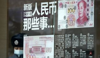 FILE - In this file photo taken Sunday, Jan. 1, 2017, a security guard wearing a protection mask against air pollution takes a rest near a bank window panel displaying the security markers on the latest Yuan note in Beijing. China's government on Tuesday, Oct. 9, 2018 promised not to weaken its currency to boost exports and rejected U.S. concern about the sagging yuan as groundless and irresponsible. (AP Photo/Andy Wong, File)