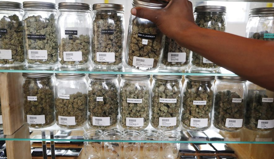 In this Tuesday, Oct. 2, 2018, photo, a clerk reaches for a container of marijuana buds for a customer at Utopia Gardens, a medical marijuana dispensary, in Detroit. Michigan and North Dakota, where voters previously authorized medical marijuana, will decide now if the drug should be legal for any adult 21 and older. They would become the 10th and 11th states to legalize so-called recreational marijuana since 2012. (AP Photo/Carlos Osorio)