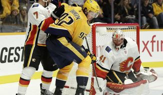 Calgary Flames goaltender Mike Smith (41) blocks a shot by Nashville Predators center Ryan Johansen (92) in the second period of an NHL hockey game Tuesday, Oct. 9, 2018, in Nashville, Tenn. (AP Photo/Mark Humphrey)
