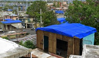 FILE - In this Oct. 19, 2017, file photo, homes in the Cantera area are covered with FEMA tarps, where buildings from the Hato Rey area stand in the background in San Juan, Puerto Rico. A new law requires the Federal Emergency Management Agency to investigate how it came to award Hurricane Maria relief contracts to a company with an unproven record. The Associated Press reported last year that the newly-formed contractor, Florida-based Bronze Star, LLC, won more than $30 million in FEMA contracts but never delivered the emergency tarps and plastic sheeting for repairs of damaged homes in Puerto Rico. (AP Photo/Carlos Giusti, File)