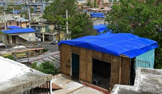 In this Oct. 19, 2017, file photo, homes in the Cantera area are covered with FEMA tarps, where buildings from the Hato Rey area stand in the background in San Juan, Puerto Rico. (AP Photo/Carlos Giusti, File)
