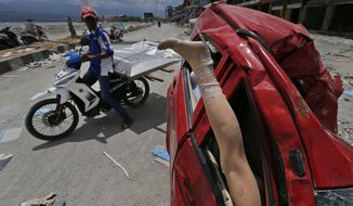 A mannequin leg sticks out from a heavily damaged car at a tsunami-ravaged area in Palu, Central Sulawesi, Indonesia, Tuesday, Oct. 9, 2018. A 7.5 magnitude earthquake rocked Central Sulawesi province on Sept. 28, triggering a tsunami and mudslides that killed a large number of people and displaced tens of thousands of others. (AP Photo/Dita Alangkara)