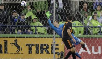 Houston Dynamo goalkeeper Joe Willis reaches for but cannot get to a goal kicked by Seattle Sounders forward Will Bruin (not shown) as Dynamo's Andrew Wenger looks on during the first half of an MLS soccer match Monday, Oct. 8, 2018, in Seattle. (AP Photo/Ted S. Warren)