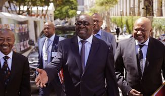 FILE - In this Wednesday, Feb. 25, 2015 file photo, South Africa's Finance Minister Nhlanhla Nene, center, arrives at parliament to deliver the annual South Africa budget speech to Parliament in Cape Town, South Africa. South Africa's finance minister has resigned after acknowledging missteps during the scandal-tainted tenure of former president Jacob Zuma. The resignation of Nhlanhla Nene was announced Tuesday, Oct. 9, 2018 by President Cyril Ramaphosa, who has pledged to clean up corruption and revive South Africa's struggling economy. (AP Photo/Schalk van Zuydam, File)