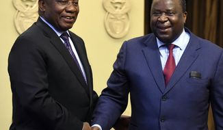 South African President Cyril Ramaphosa, left, shakes hand with newly elected Finance Minister, Tito Mboweni, in Cape Town, South Africa, Tuesday, Oct.9 2018. Former finance minister Nhlanhla Nene resigned after acknowledging missteps during the scandal-tainted tenure of former president Jacob Zuma. (AP Photo)