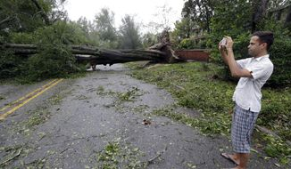 FILE - In a  Friday, Sept. 14, 2018 file photo, Shane Fernando takes a photo of fallen trees near his home in Wilmington, N.C., after Hurricane Florence made landfall.  Fernando is worried about the approach of Hurricane Michael because he sustained tree damage to his house in Florence and has tarps covering parts of the exterior.  (AP Photo/Chuck Burton, File)