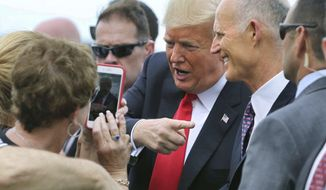 Accompanied by Florida governor Rick Scott, President Trump is welcomed at Orlando International Airport, Monday, Oct. 8, 2018. Trump is scheduled to deliver remarks to the International Association of Chiefs of Police, at the Orange County Convention Center, in Orlando, Fla. (Joe Burbank/Orlando Sentinel via AP)