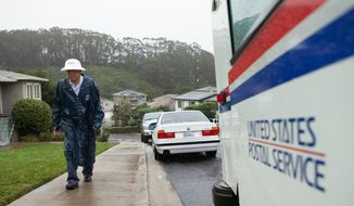 In this Dec. 11, 2014, file photo, Danny Joe delivers mail in the rain in San Bruno Calif. (AP Photo/Alex Washburn, File)