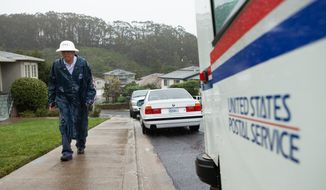 FILE - In this Dec. 11, 2014 file photo, Danny Joe delivers mail in the rain in San Bruno Calif. Political campaign mailings and an increase in holiday package deliveries helped boost U.S. Postal Service revenue at the end of 2014, even as the agency posted a $754 million loss in  the final three months of the year. Still, Postmaster General Megan Brennan said that despite continuing losses, the outlook is much brighter than it has been in the past. (AP Photo/Alex Washburn, File)