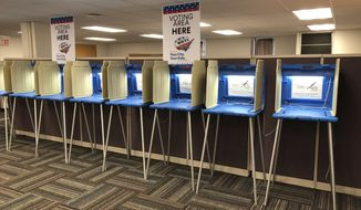 In this Sept. 20, 2018 photo, voting booths stand ready in downtown Minneapolis for the opening of early voting in Minnesota. Minnesota and South Dakota are tied for the earliest start in the country for early voting in the 2018 midterm elections. A new poll finds that a large majority of Americans are concerned the nation's voting systems might be vulnerable to hackers, with Democrats more concerned than Republicans.  (AP Photo/Steve Karnowski)