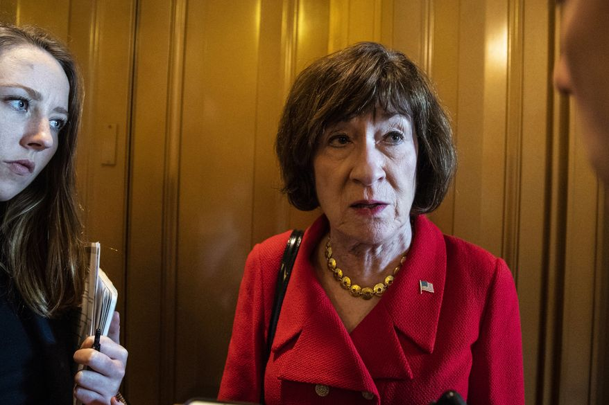 Sen. Susan Collins, R-Maine, right, talks with a reporter on Capitol Hill, Wednesday, Oct. 10, 2018 in Washington. (AP Photo/Alex Brandon)