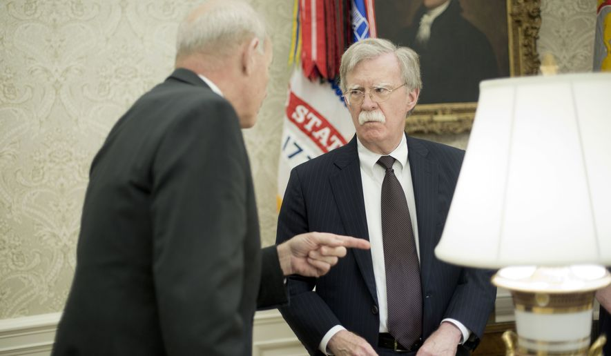 White House Chief of Staff John Kelly, left, talks with, White House National Security Advisor John Bolton, right, in the Oval Office of the White House in Washington during President Donald Trump's meeting to discuss potential damage from Hurricane Michael, Wednesday, Oct. 10, 2018. (AP Photo/Pablo Martinez Monsivais)