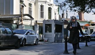 A woman walks past Saudi Arabia's consul's residence, in Istanbul, Wednesday, Oct. 10, 2018. A Turkish television station has aired surveillance video of missing writer Jamal Khashoggi walking into the Saudi Consulate in Istanbul and a black van leaving later for the consul's home. (AP Photo/Lefteris Pitarakis)