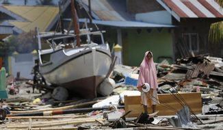 A woman stands in the rubble of houses as a boat swept ashore by tsunami rests on the ground in the background in Wani village on the outskirt of Palu, Central Sulawesi, Indonesia, Wednesday, Oct. 10, 2018. A 7.5 magnitude earthquake rocked Central Sulawesi province on Sept. 28, triggering a tsunami and mudslides that killed a large number of people and displaced tens of thousands of others. (AP Photo/Dita Alangkara)
