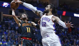 FILE - In this Oct. 7, 2018, file photo, Oklahoma City Thunder center Steven Adams (12) blocks a shot by Atlanta Hawks guard Trae Young (11) in the first half of an NBA preseason basketball game in Tulsa, Okla. The narrative on the demise of the big man in the NBA may have been a bit premature. At the very least it has been misinterpreted. Their roles have been defined, but Steven Adams, DeMarcus Cousins, Anthony Davis, Nikola Jokic, Clint Capela and others have shown teams still covet a dominant center. (AP Photo/Sue Ogrocki, File)