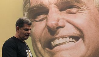 Backdropped by a picture of the presidential candidate Jair Bolsonaro of the Social Liberal Party, Gustavo Bebianno Rocha, president of the Social Liberal Party, arrives to speak to journalists after his candidate spoke in a live broadcast on Facebook, at a hotel in Rio de Janeiro, Brazil, Sunday, Oct. 7, 2018. Official results showed that Workers' Party candidate Fernando Haddad will face Jair Bolsonaro, the far-right congressman in a second-round vote. (AP Photo/Leo Correa)