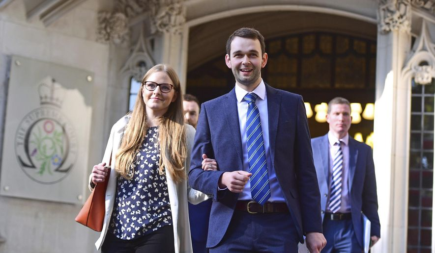Ashers bakery owners Daniel and Amy McArthur outside the Supreme Court in London, Wednesday Oct. 10, 2018. Britain's Supreme Court said Wednesday Oct. 10, 2018, the bakery owned by a Christian family didn't discriminate against a gay customer when they refused to make a cake supporting same-sex marriage. (Victoria Jones/PA via AP)
