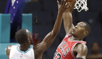 Charlotte Hornets' Kemba Walker (15) shoots over Chicago Bulls' Cameron Payne (22) in the first half of a preseason NBA basketball game in Charlotte, N.C., Monday, Oct. 8, 2018. (AP Photo/Chuck Burton)