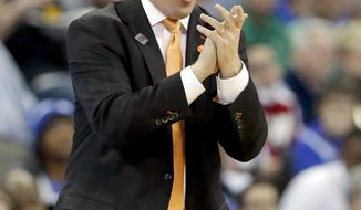 FILE - In this March 23, 2018, file photo, Clemson head coach Brad Brownell gestures on the sidelines during the first half of a regional semifinal game against Kansas in the NCAA men's college basketball tournament, in Omaha, Neb. Brownell enjoyed a school record 11 Atlantic Coast Conference wins, a run to the NCAA Tournament's Sweet 16 and new contract  extension tying him to the Tigers through 2024. Security is nice, but Brownell wants to keep producing success on the court.(AP Photo/Charlie Neibergall, File)