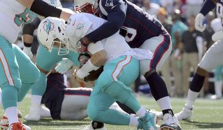 FILE - In this Sept. 30, 2018, file photo, New England Patriots defensive tackle Adam Butler, right, sacks Miami Dolphins quarterback Ryan Tannehill (17) during the second half of an NFL football game, in Foxborough, Mass. Tannehill has been taking a pounding. He and the Dolphins will try and regroup for Sunday's game against Chicago(AP Photo/Elise Amendola, File)