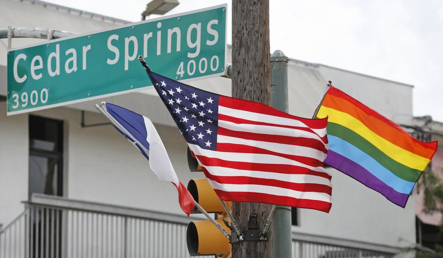 This Monday, Oct. 8, 2018, photo shows flags flying at the intersection of Cedar Springs Road and Throckmorton Street in Dallas, where a historic marker commemorating the city's LGBT community was installed Wednesday. For most Dallasites, the city's LGBT history begins and ends in Oak Lawn, along Cedar Springs Road, where people march in parades and in protests. (Louis DeLuca/The Dallas Morning News via AP)